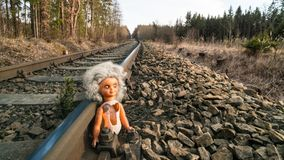 Broken abandoned doll on train rail in sunny forest landscape. Lost child toy at the old rusty railroad track. The concept of danger, childhood, fate, accident Royalty Free Stock Photos