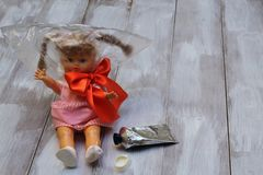 Lost childhood. Drugs and children. Doll with plastic bag, red satin bow, glue tube on light wooden background stock photo