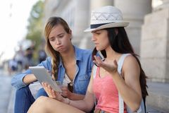 Lost and confused girl friends looking for directions on map. Girl Royalty Free Stock Photo