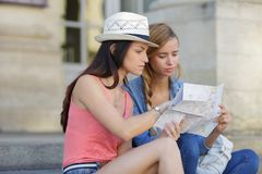 Lost and confused girl friends looking for directions on map Stock Photography