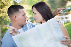 Lost and Confused Mixed Race Couple Looking Over Map Outside Stock Image
