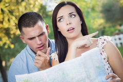 Lost and Confused Mixed Race Couple Looking Over Map Outside. Lost and Confused Mixed Race Couple Looking Over A Map Outside Together Stock Photography