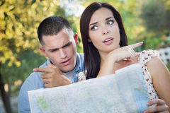 Lost and Confused Mixed Race Couple Looking Over Map Outside. Lost and Confused Mixed Race Couple Looking Over A Map Outside Together Stock Photos