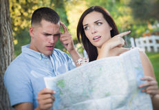Lost and Confused Mixed Race Couple Looking Over Map Outside. Lost and Confused Mixed Race Couple Looking Over A Map Outside Together Stock Images