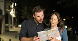 Lost couple searching location in a map in the night stock video footage