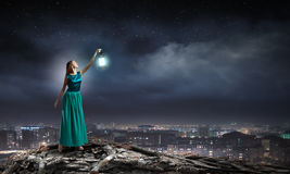 Lost in darkness. Young woman in green dress with lantern walking in darkness Royalty Free Stock Images