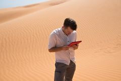 Lost in the desert. Caucasian man sitting on sand with tablet. He is lost and looking in map where to go. Lost in the desert. Caucasian man standing on sand with royalty free stock photos