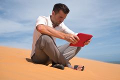 Lost in the desert. Caucasian man sitting on sand with tablet. He is lost and lookking in map where to go. Find way in fifficult situation royalty free stock photography