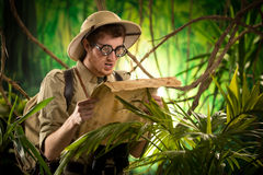 Lost explorer with old map. Lost explorer with glasses holding an old map looking for the right direction Royalty Free Stock Photo