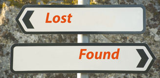 Lost and found. An image of two signs on a post one pointing to lost and the other to found. The words are in orange text on a white background stock photos
