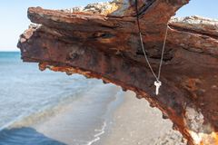 Silver worn key hanging on some cord from a rusty shipwreck stock photos