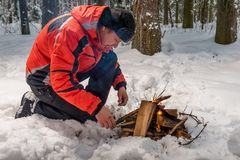 A lost frozen tourist tries to build a fire. In a winter cold forest Royalty Free Stock Images