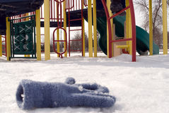 Lost Glove. A lost glove laying in the snow in front of a childrens playground equipment Royalty Free Stock Photos