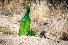 Lost green bottle in sand Royalty Free Stock Images
