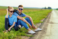 Lost haghway. Hitchhiking couple. Happy young people sitting by the highway Stock Photography