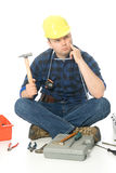 Lost handyman. Handyman on the floor surrounded with his tools (and meter around his neck) think what he need to do but his lost in that attempt Stock Photography