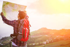 Lost hiker with backpack checks map to find directions. In wilderness area royalty free stock photo