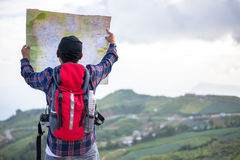 Lost hiker with backpack checks map to find directions Stock Images