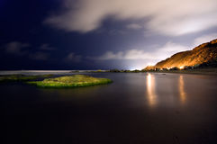 Lost on an island. Bonfires on the beach at night, and green rocks Stock Image