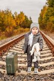 Lonely little boy in vintage clothes hugs a bunny next to an old-fashioned suitcase in the middle of the forest on an abandoned ra royalty free stock photos