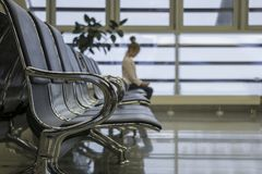 Lost, lonely child. Departure lounge at the airport. Airport terminal, empty waiting chairs. royalty free stock image