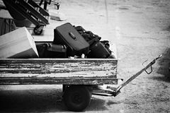 Lost luggage. Sitting in an old wagon on the tarmac, converted to bw with focus on baggage Royalty Free Stock Photos