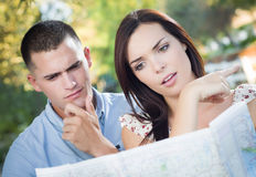 Lost Mixed Race Couple Looking Over Map Outside Royalty Free Stock Images