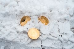 The lost money. Copprito coins of gold bitcoin are lying on the snow. No one needed. In winter on the road, traces of. The lost money. Copprito coins of gold royalty free stock image