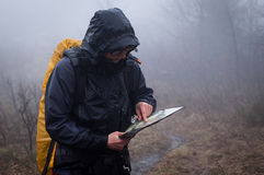 Lost in the mountains. Young woman reading a map in the misty evening Stock Photography
