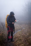 Lost in the mountains. Young woman reading a map in the misty evening Royalty Free Stock Image