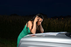 Lost at Night. Image of a female looking at a map spread out on the hood of  a car Royalty Free Stock Images