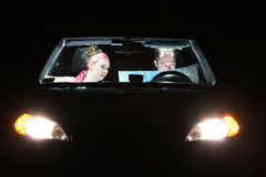 Lost at night. A couple in a  car looking at a map Stock Images