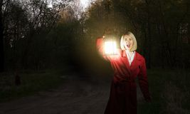 Lost in night. Young woman in red cloak with lantern lost in forest Royalty Free Stock Image
