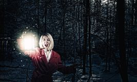 Lost in night. Young woman in red cloak with lantern lost in forest Stock Photography