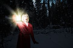 Lost in night. Young woman in red cloak with lantern lost in forest Royalty Free Stock Images