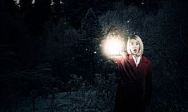 Lost in night. Young woman in red cloak with lantern lost in forest Stock Photos