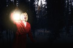 Lost in night. Young woman in red cloak with lantern lost in forest Stock Photo