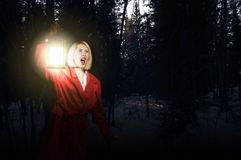 Lost in night. Young woman in red cloak with lantern lost in forest Royalty Free Stock Photo