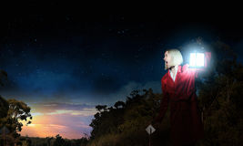 Lost in night. Young woman in red cloak with lantern lost in forest Stock Image