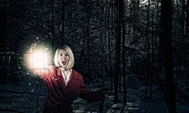 Lost in night. Young woman in red cloak with lantern lost in forest Stock Images