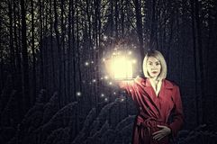 Lost in night. Young woman in red cloak with lantern lost in forest Royalty Free Stock Photography