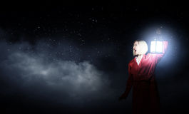 Lost in night. Young woman in red cloak with lantern lost in forest Royalty Free Stock Photos