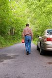 Lost No Gas. A man is lost, on a country road and has run out of gasoline in his car.  He's walking down the road with a gas can in his hand, his car on the side Royalty Free Stock Image