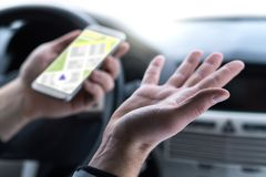 Lost and no GPS connection. Navigation problem. Man using smartphone map application in car. Clueless and confused driver spreading hands. Slow internet or bad stock photo
