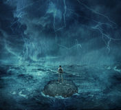 Lost in the ocean. Lost man standing abandoned on a rock island in middle of the ocean, in a stormy night with lightnings in the sky. Looking for help, trying to Stock Image