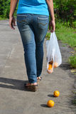 Lost Oranges. A young lady walking in the street with a broken shopping bag royalty free stock photos
