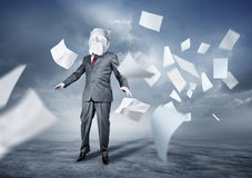 Lost In Paperwork. A businessman's face covered in paperwork. Business concept Royalty Free Stock Photo