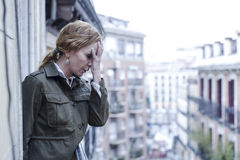 Lost and sad woman at home balcony suffering depression looking thoughtful and solitary Stock Images