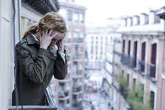 Lost and sad woman at home balcony suffering depression looking thoughtful and solitary. In female depression concept and sadness emotion dramatic facial royalty free stock photo