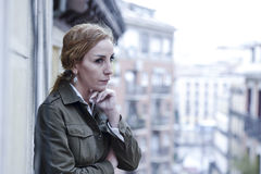 Lost and sad woman at home balcony suffering depression looking thoughtful and solitary. In female depression concept and sadness emotion dramatic facial stock image